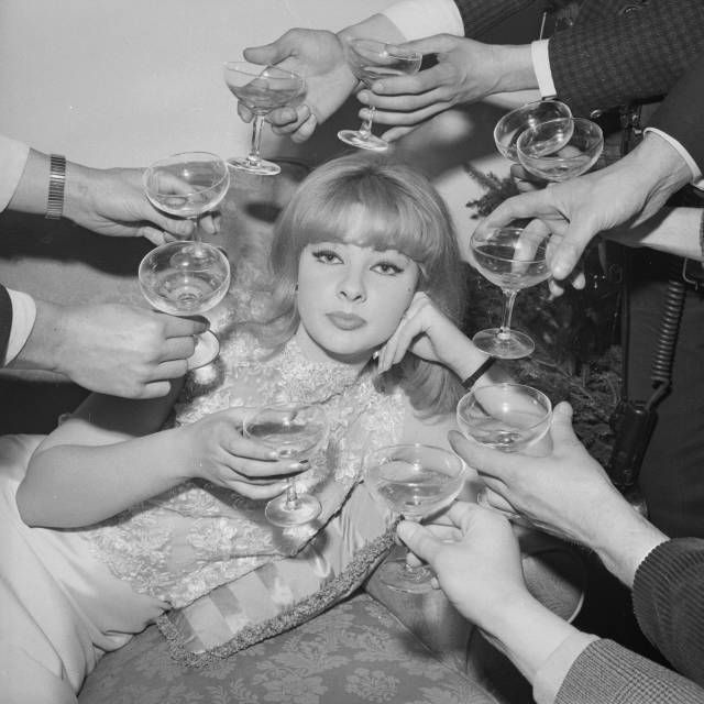 31st December 1963: Mandy Rice-Davies, a Welsh showgirl and witness in the Profumo affair, surrounded by champagne at the press launch of her book 'The Mandy Report'. (Photo by Harry Dempster/Express/Getty Images)